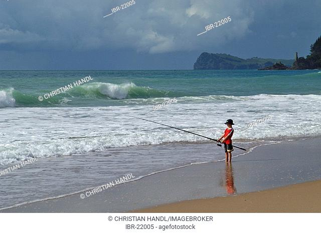 Fishing kid in Cathedral Cove on Coromandel Peninsula New Zealand