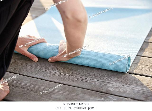 Woman rolling exercise mat