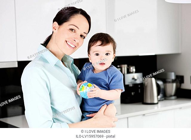 A mother with her baby son, baby holding a globe ball