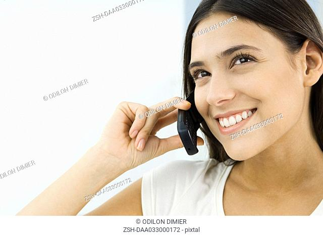 Woman using cell phone, looking up and smiling