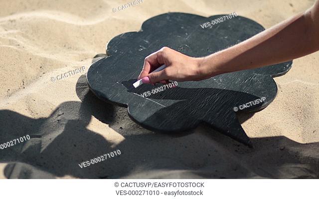 Female hand writting word family on black board