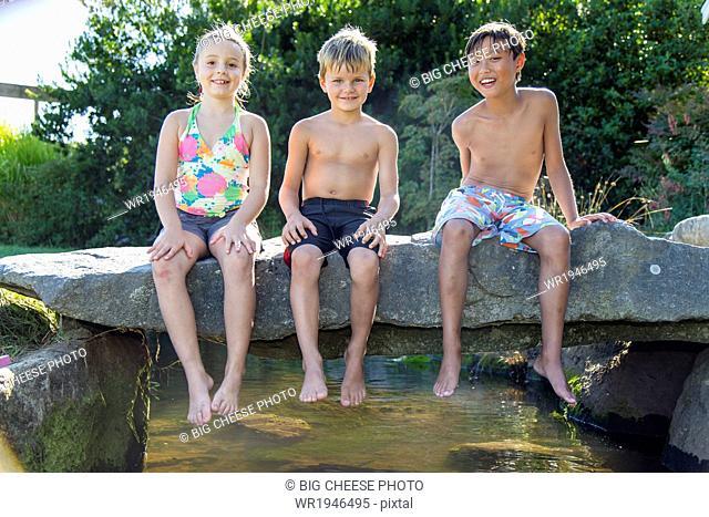 Three children sitting on a stone bridge over a small creek