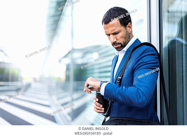 Businessman with cup of coffee, looking on his watch
