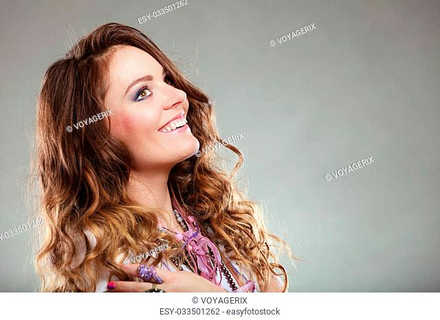 Happy pretty young woman wearing many plenty of jewelry necklaces beads. Portrait of gorgeous fashion girl in studio on gray