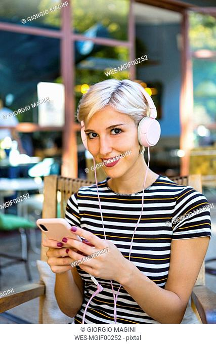 Portrait of smiling young woman with smartphone listening music with headphones at pavement cafe