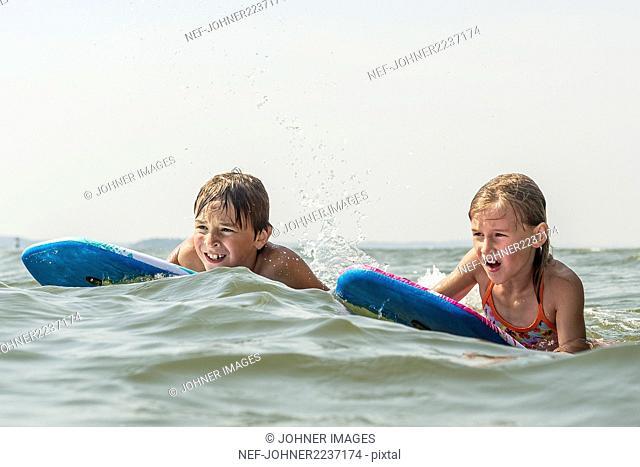Boy and girl bodyboarding