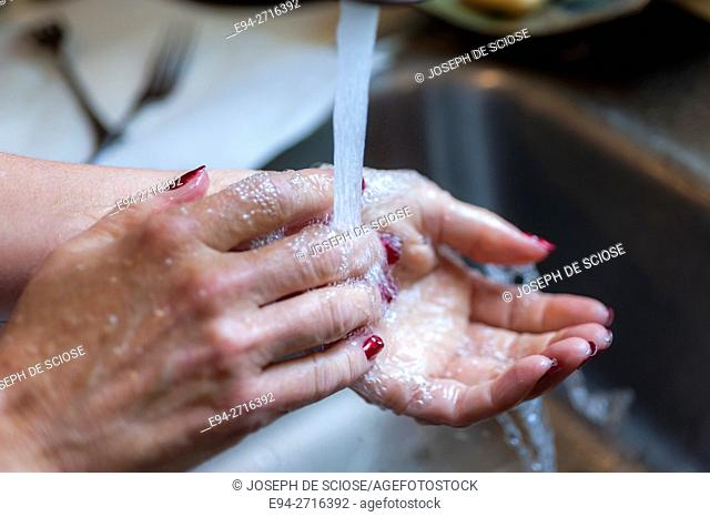 Woman's hands being washed over a sink
