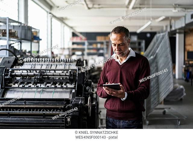 Mature man in a printing shop using digital tablet