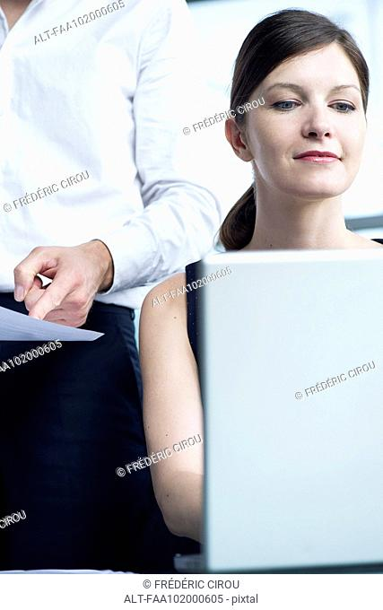 Woman working on laptop computer, boss watching over her shoulder