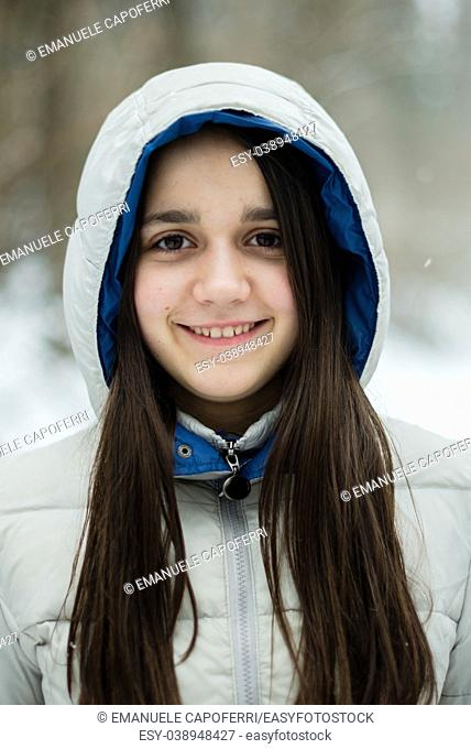 portrait of an 11-year-old girl outside under a snowfall, in a forest, dressed in a down jacket, a windbreaker
