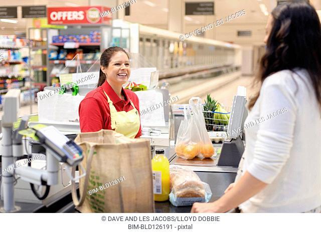Hispanic woman helping customer at grocery checkout