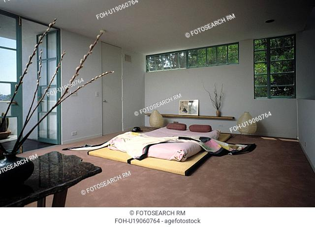 Pink futon on tatami mats below long window in modern Japanese-style bedroom with brown carpet