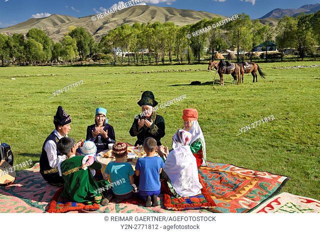 Traditional Kazakh family saying grace at a picnic in Chilik river valley Saty Kazakhstan