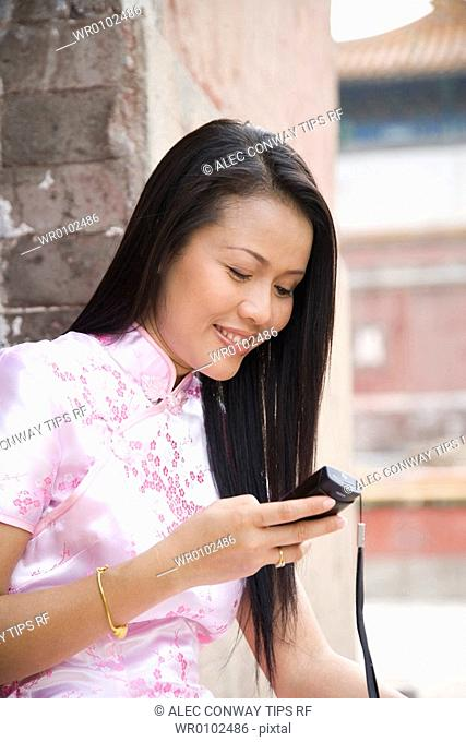 China, Bejing, the Summer Palace, asian woman with mobile