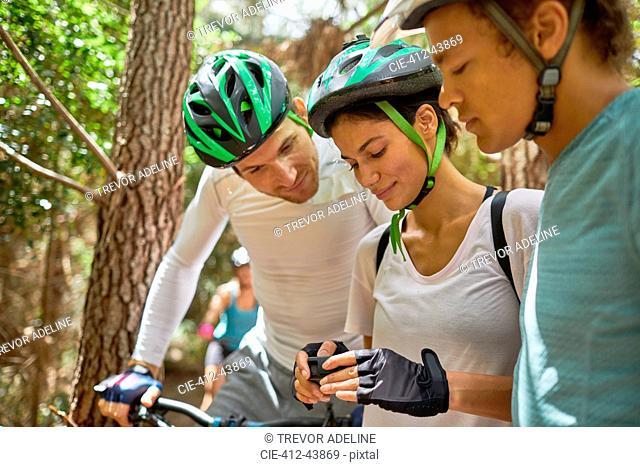 Friends mountain biking, checking wearable camera