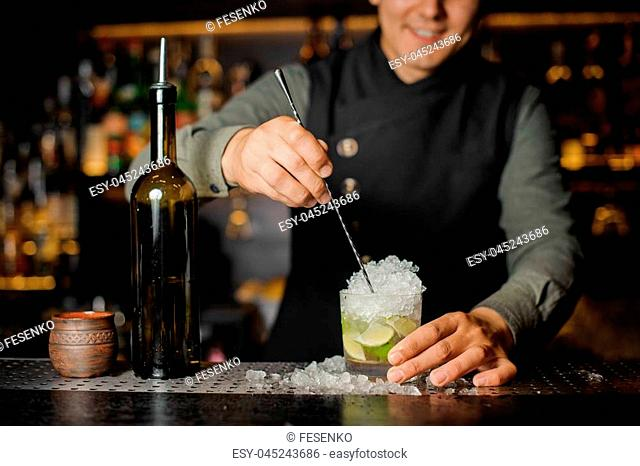 Barman stiring a fresh delicious cocktail with lime and cane sugar in a cocktail glass on the bar counter