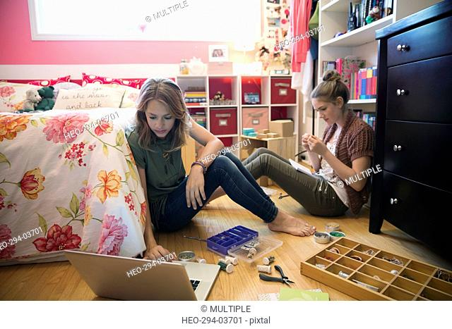 Girls making jewelry in bedroom