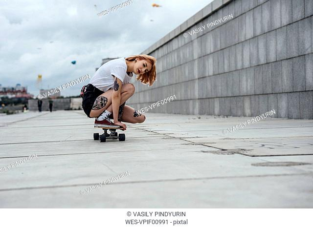 Young woman crouching on carver skateboard on a promenade