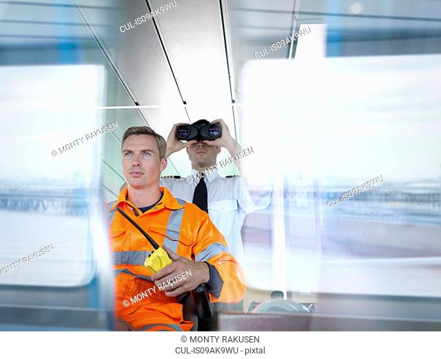 Ship worker and captain using binoculars on ship's bridge with reflections on window