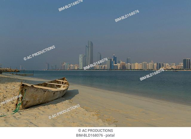 Canoe on beach near city skyline, Abu Dhabi Emirate, United Arab Emirates
