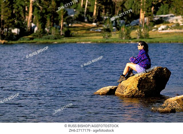 Woman sitting on a rock along the shore of Boothe Lake, Yosemite National Park, California USA