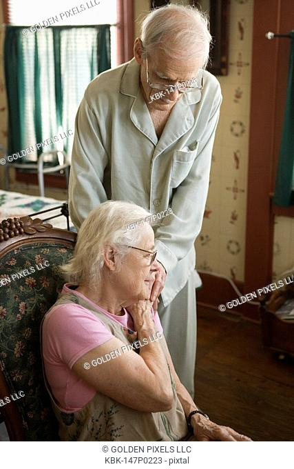 Elderly couple comforting each other