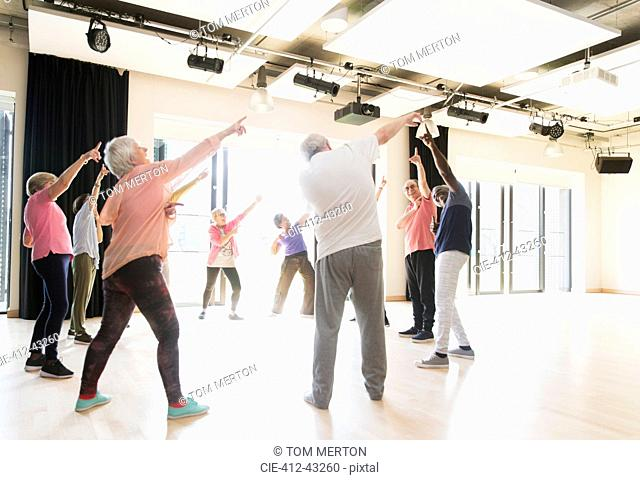 Active seniors dancing, exercising and stretching in circle
