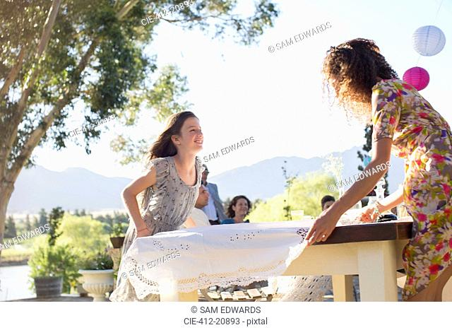 Mother and daughter laying table cloth on table