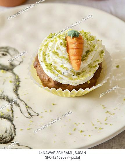 A carrot cupcake with butter cream, pistachios and a marzipan carrot