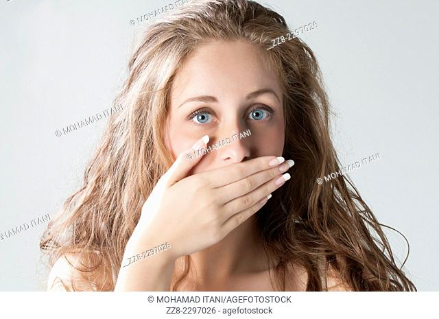 Beautiful young woman hand covering mouth