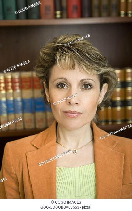 Businesswoman seated in front of wall of books