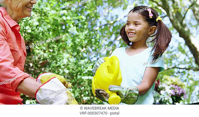 Grandmother and grand daughter watering plants