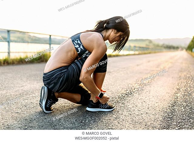 Woman tying laces of sports shoes