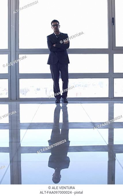 Businessman learning against high rise window, backlit by sunset glow