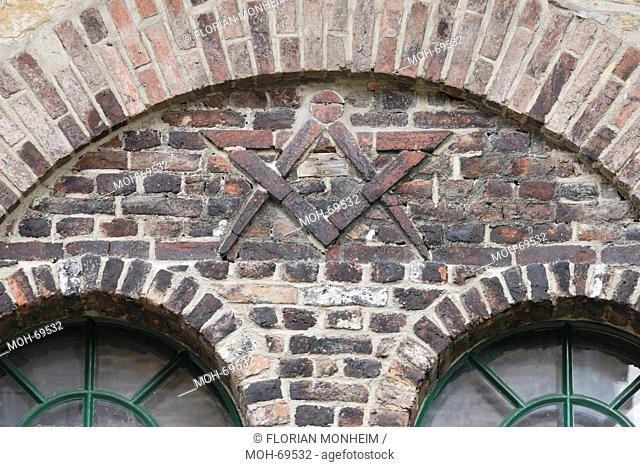 Tür der ehemaligen Schmiedewerkstatt, Mauerrelief mit Stechzirkel und Zeichendreieck, eventuell Handwerkerzeichen