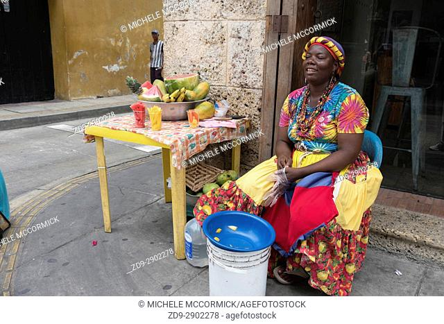 A woman prepares fruit for sale on the street in Cartagena