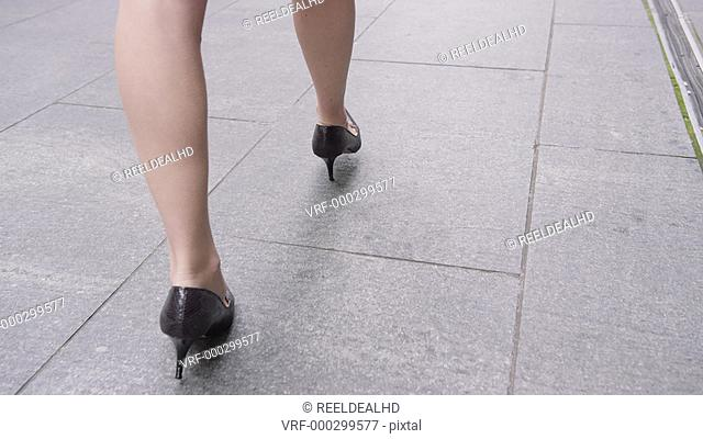 Close-up businesswoman's feet in heels walking down pavement in city to work