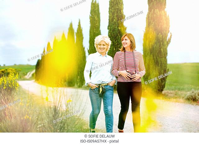 Two mature female friends strolling on rural road, Tuscany, Italy