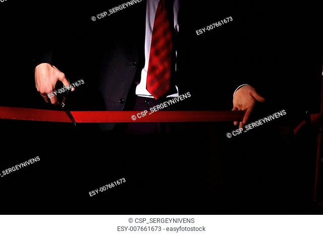 Businessman with scissors cuting a red ribbon