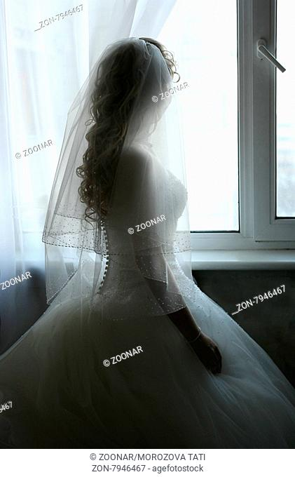 The beautiful bride prepares for wedding. Silhouette on a background of a window