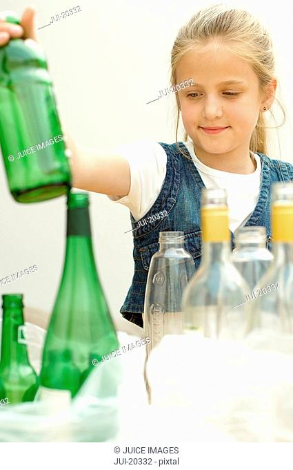 Girl separating green plastic bottle clear glass bottle, Den Haag, Netherlands