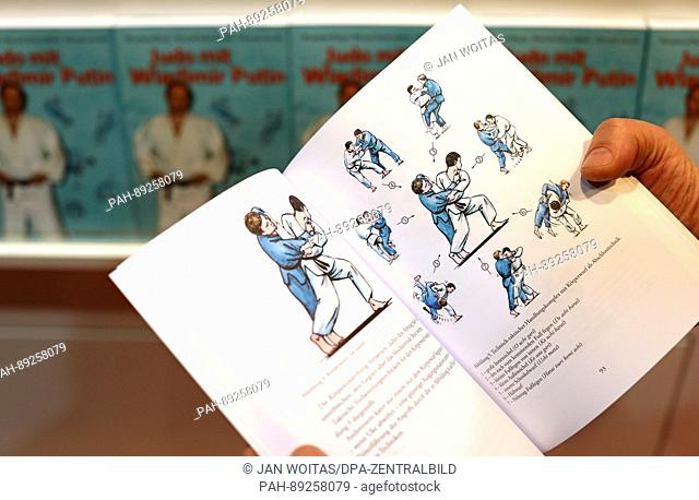 """The opened book """"""""Judo with Vladimir Putin""""""""can be seen at the book fair in Leipzig, Germany, 23 March 2017. With 221 pages and 77 coloured illustrations"""