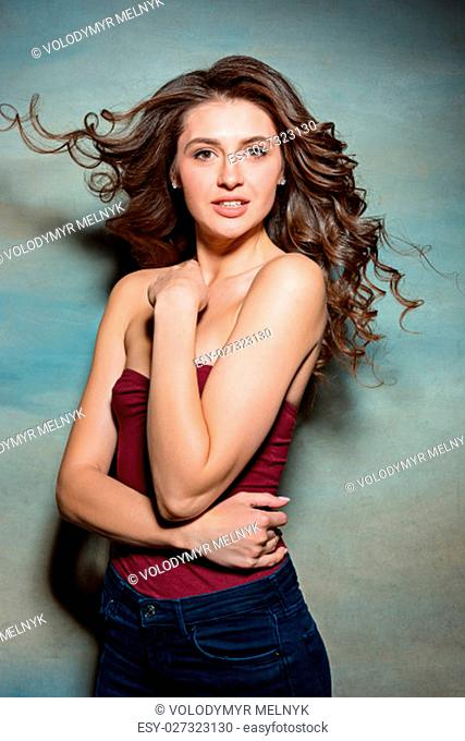 Pretty girl with long hair smiling, enjoying life, posing on gray studio background