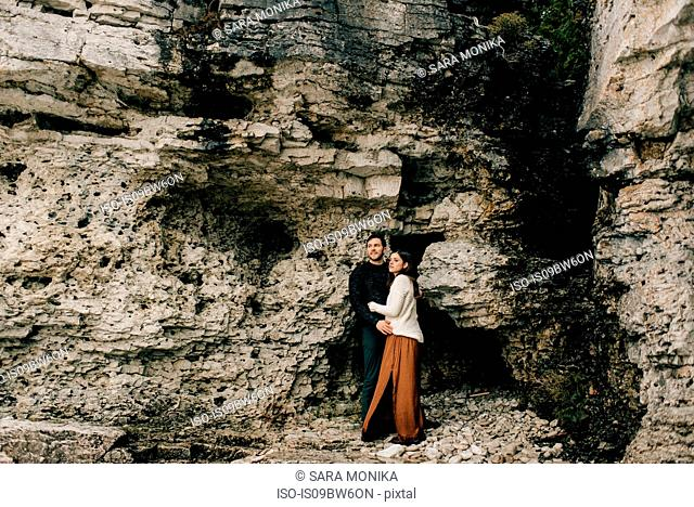 Couple hugging beside rock face, Tobermory, Canada
