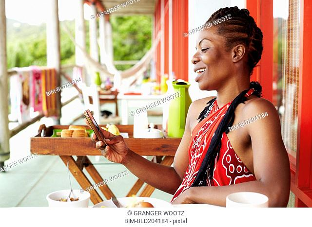 Black woman using cell phone at lunch