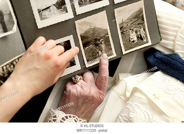 Old woman showing photo album, close-up