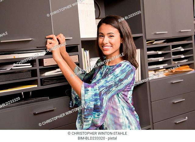 Smiling Hispanic businesswoman opening office cabinet