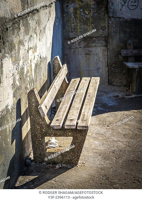 A memorial wooden bench in a secluded corner of a pedestrian walkway. Vandalised. In need of repair, Cape Town, South Africa