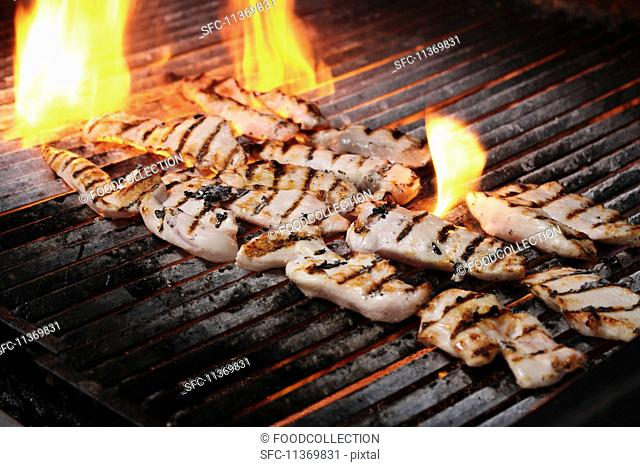 Chicken fillets on flaming a charcoal grill
