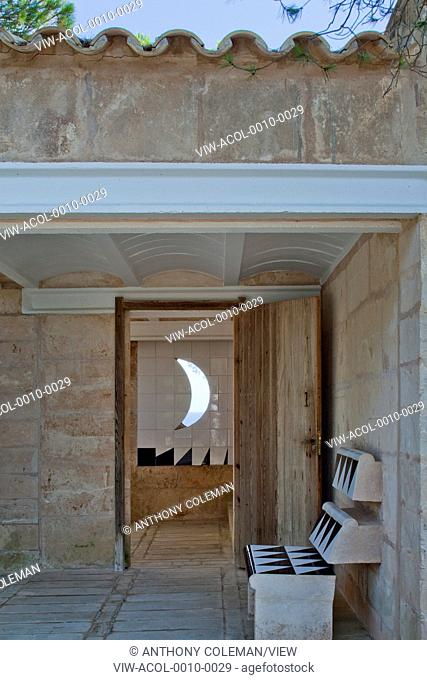 Can Lis, Mallorca, Spain. Architect: Utzon, Jorn, 1971. Front door showing built in furniture and crescent shaped window off entrance patio courtyard